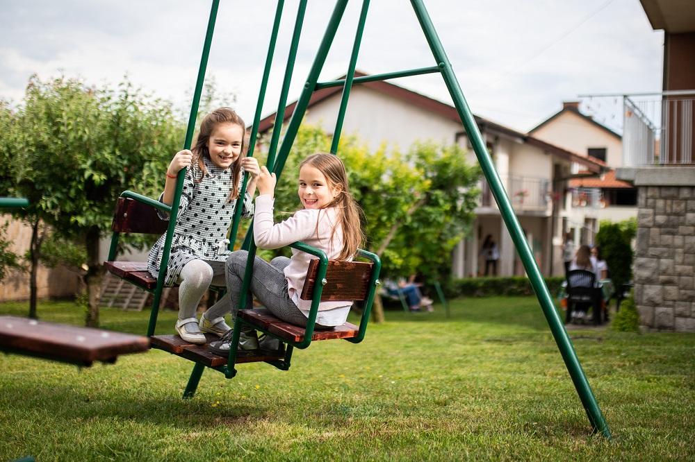 Dve devojcice se ljuljaju na dvoristu